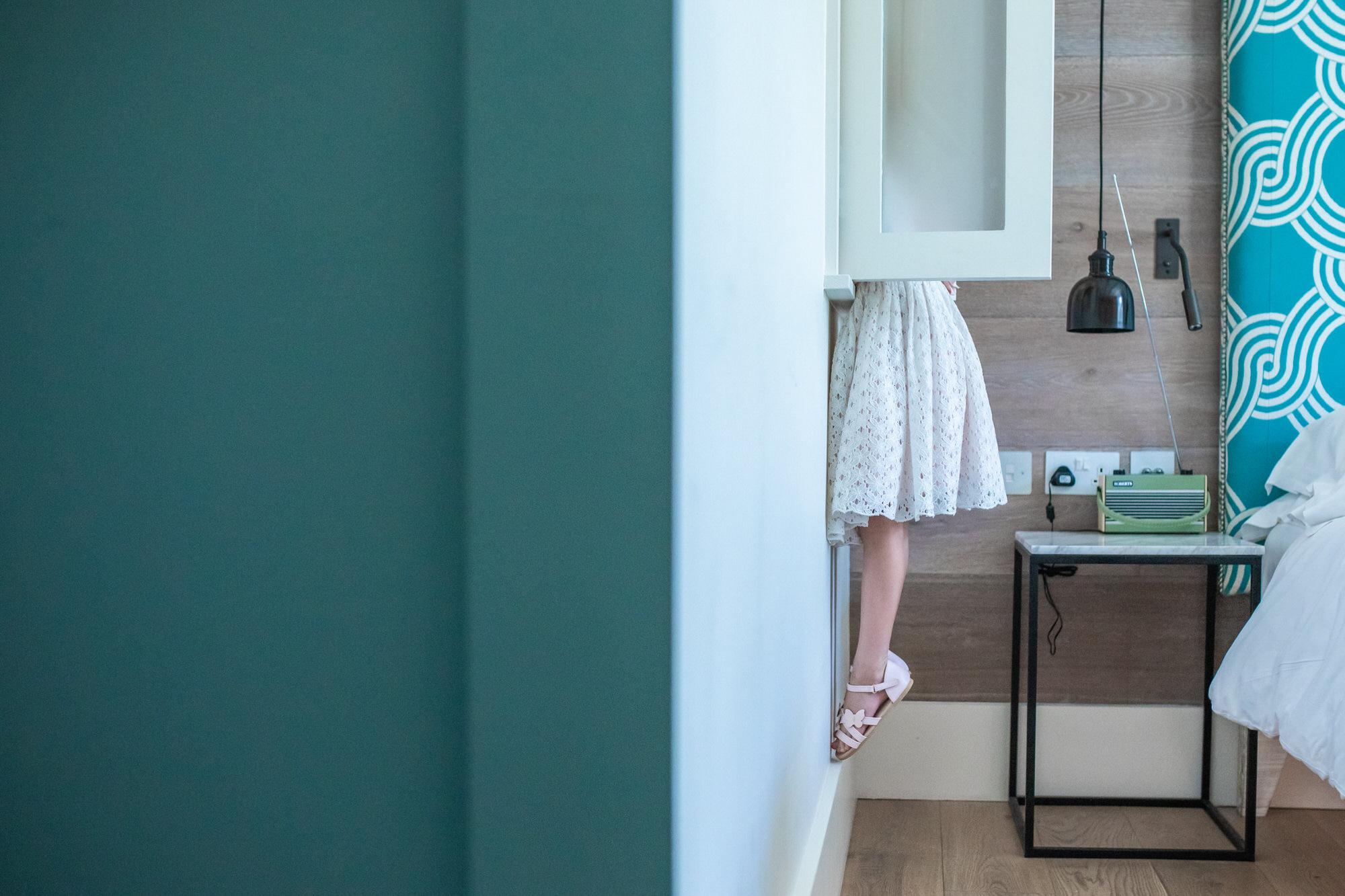 child in dress peeking through window, photographed by Hitchin christening photographer