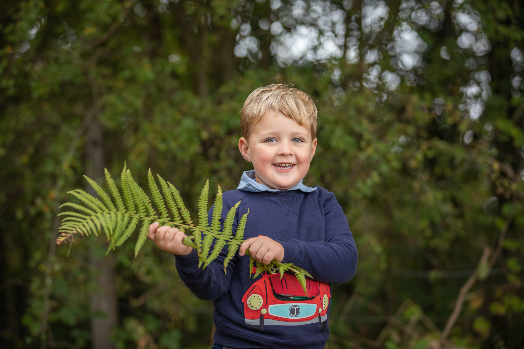 a boy smiles at his Welwyn family photo shoot, taken by Hertfordshire family photographer