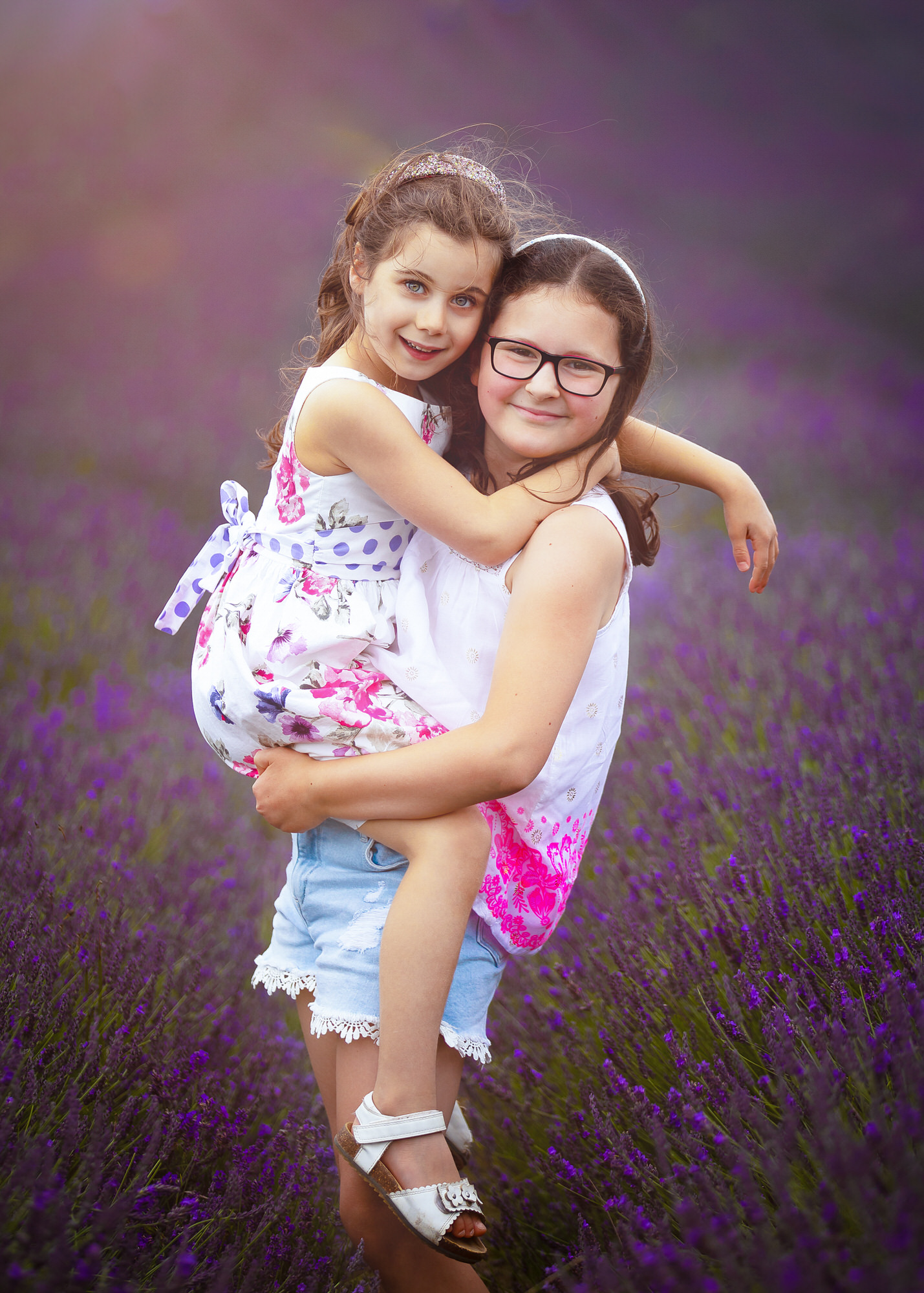a sister carries her sibling at their family photo shoot at Hitchin lavender farm