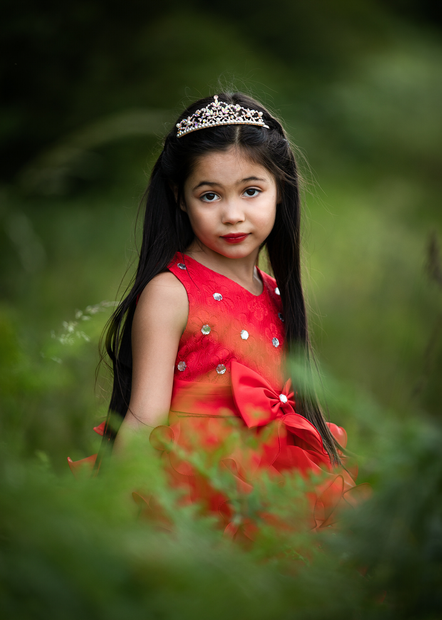 a girl in red poses outdoors at a photo shoot with hertfordshire photographer
