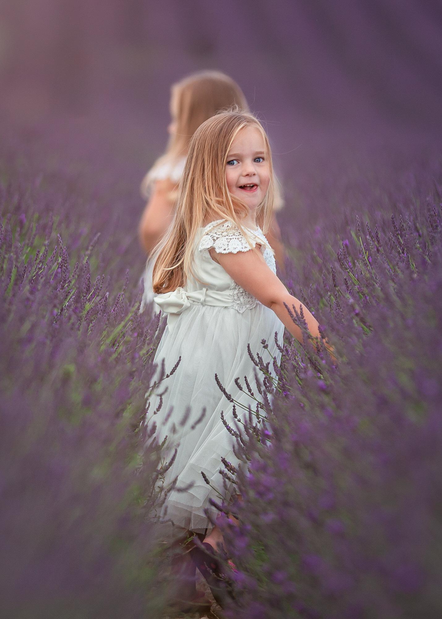 Two girls walk through HItchin lavender farm at a lavender photo shoot in hertfordshire