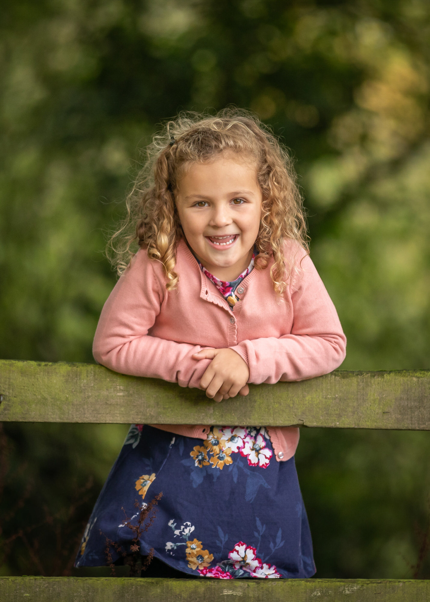 a girl leans on a fence at her Hertfordshire family photo shoot