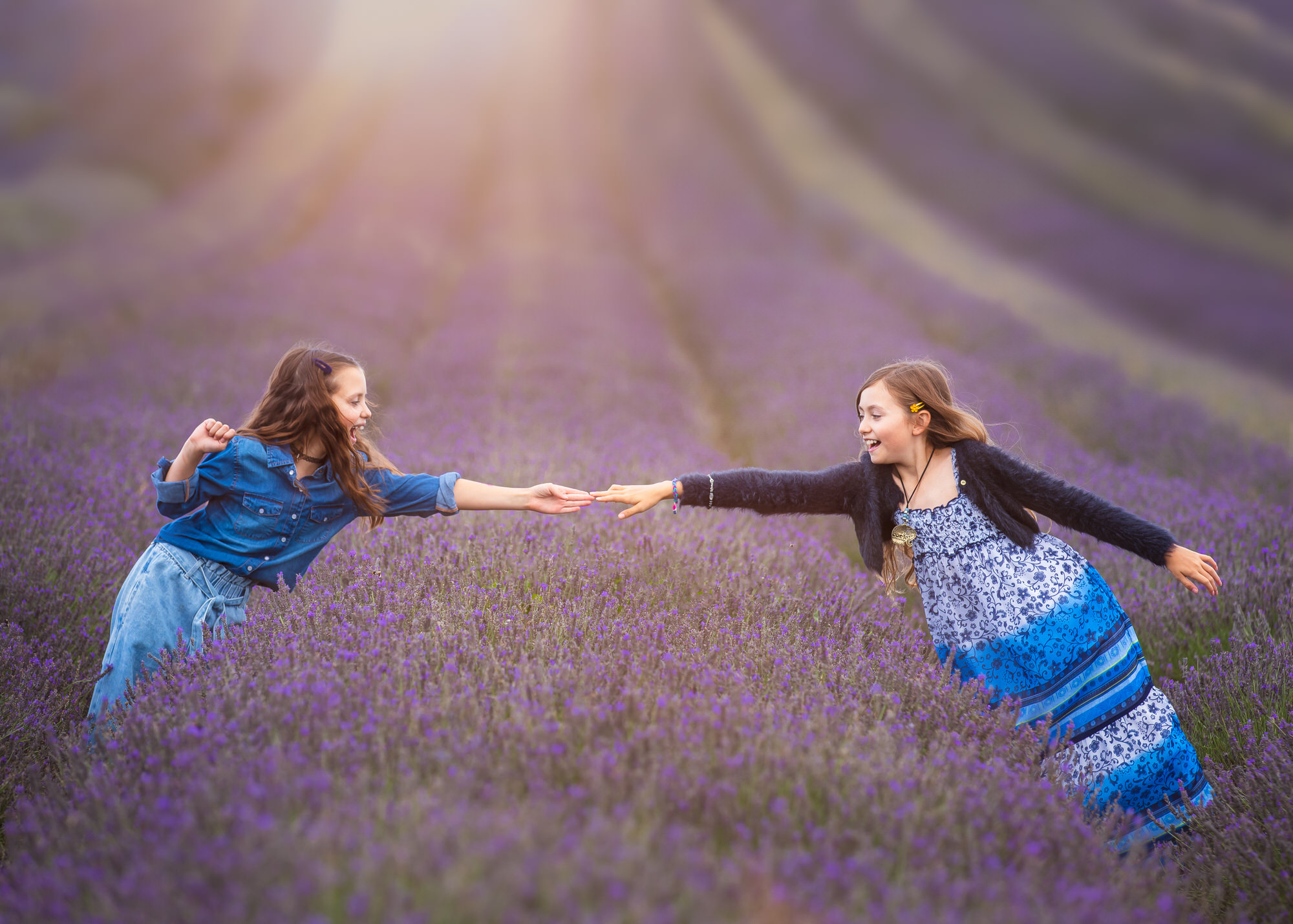 two girls reach towards each other at Hitchin lavender farm, at a lavender photo shoot