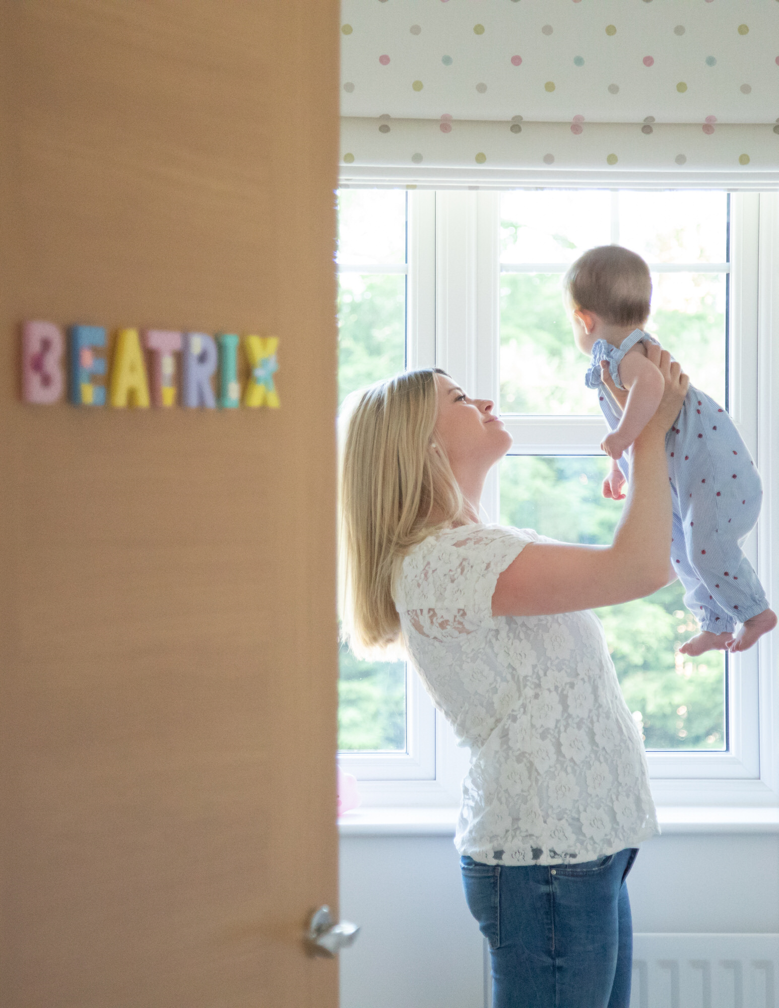 mother holding baby during photo shoot at home, photographed by Welwyn baby photographer