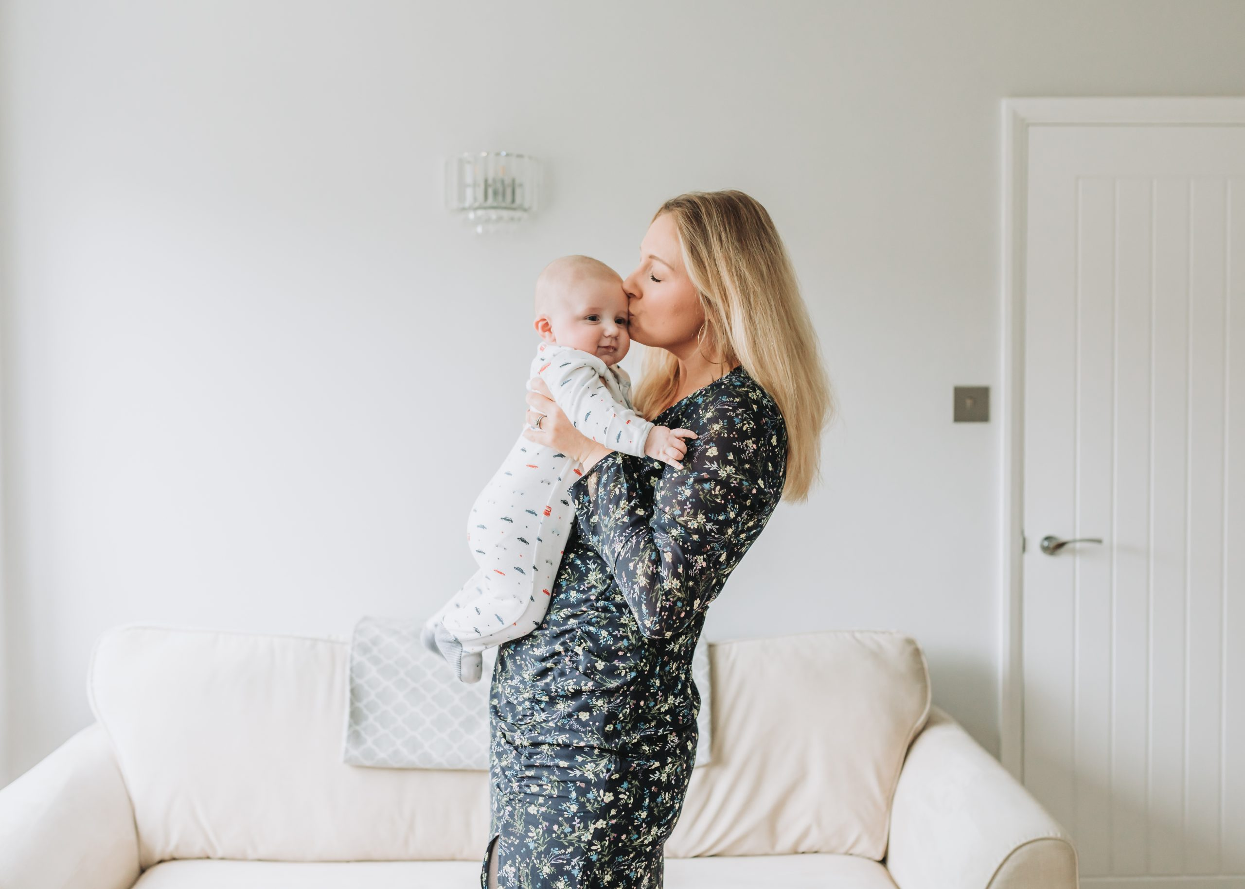 Mother kissing her new baby at a photo shoot at home, photographed by Stevenage family photographer Alannah Hebbert