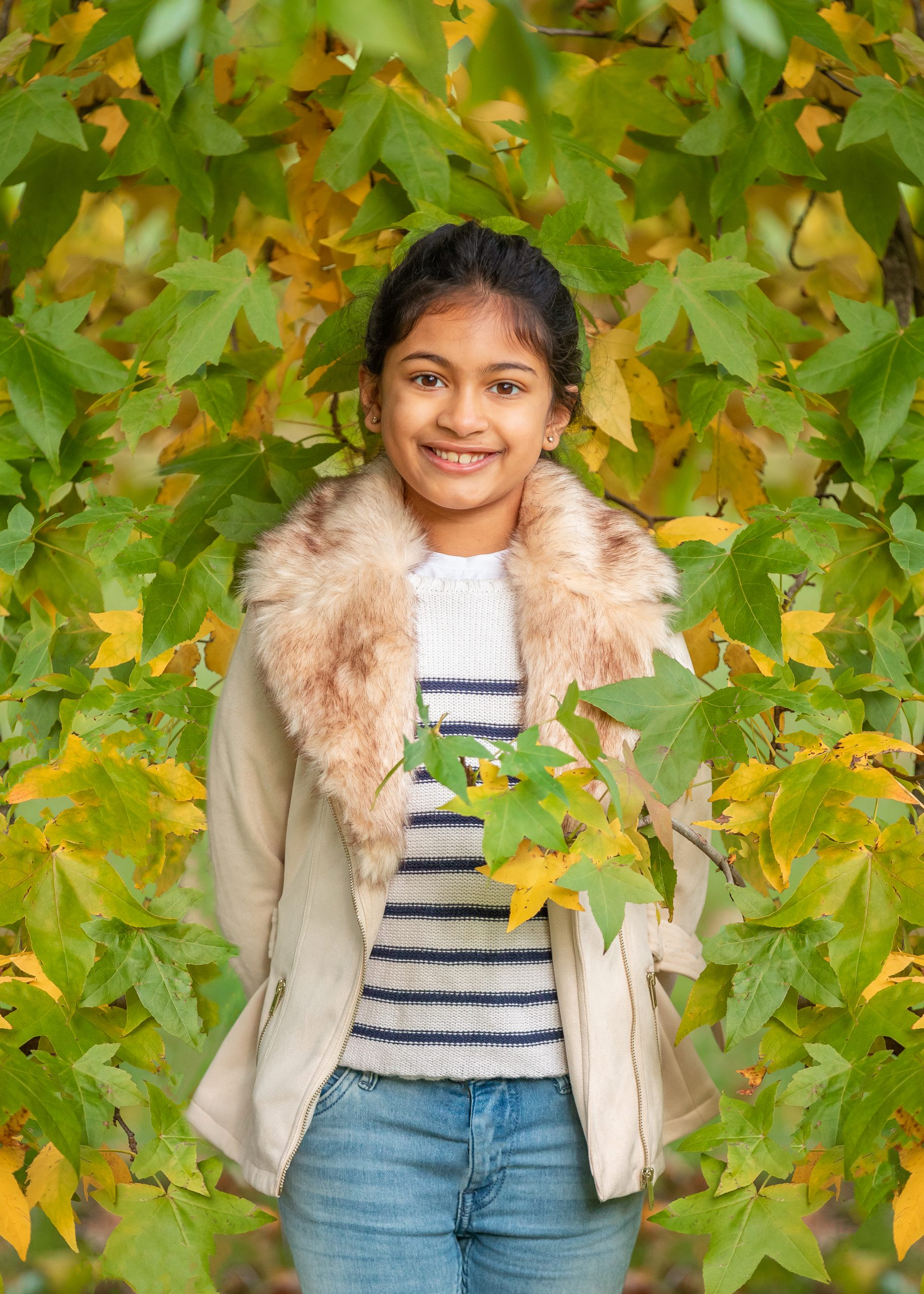 A girl stands by a tree, taken by a Hertfordshire family photographer