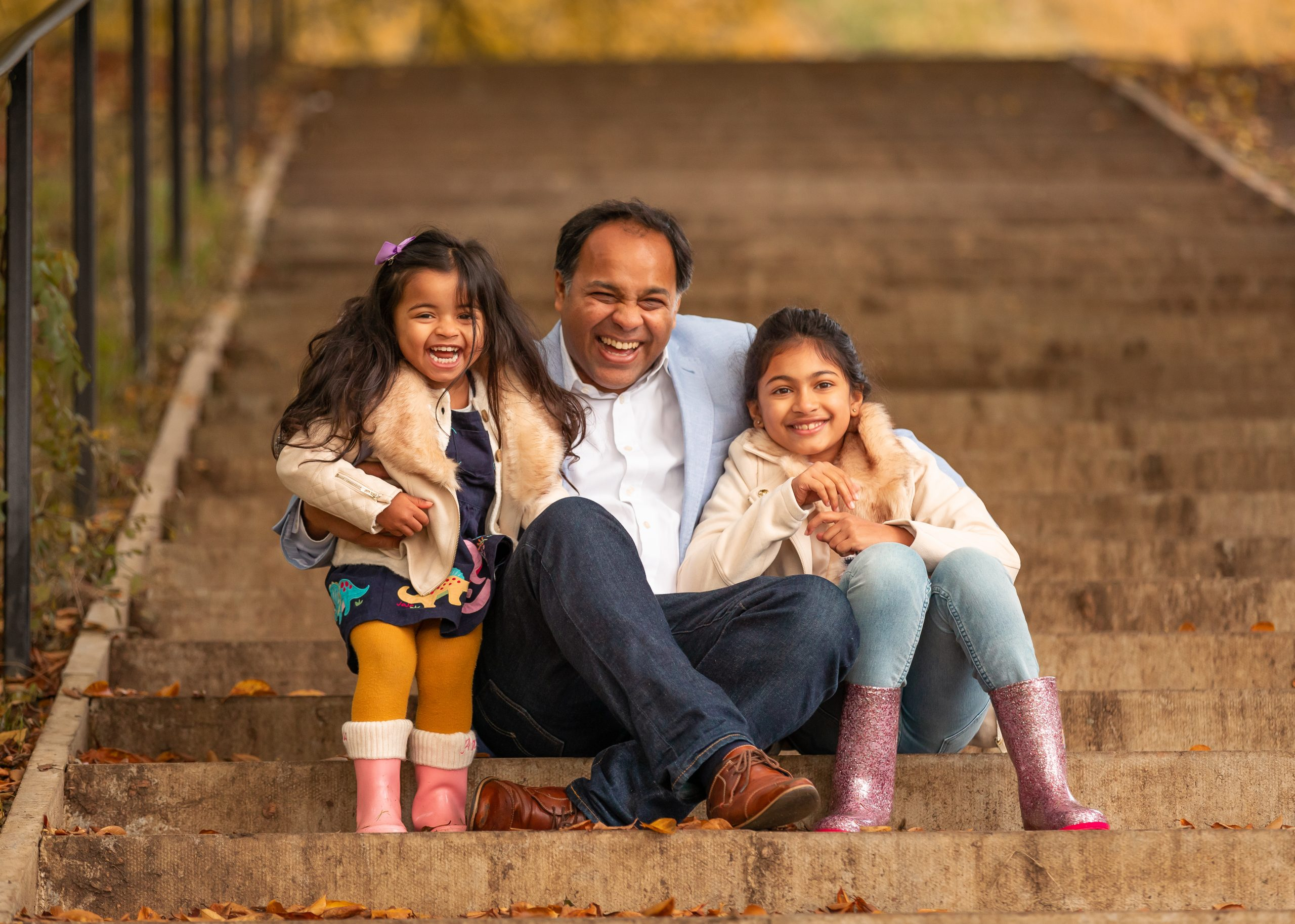 A dad laughs with his daughters at a Kenwood House photo shoot