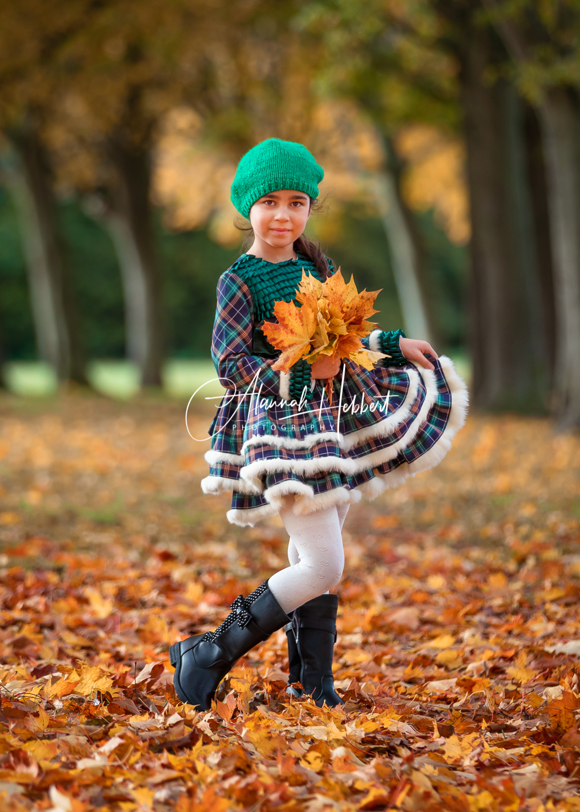 a girl stands with autumn leaves, photographed by Stevenage child photographer Alannah Hebbert